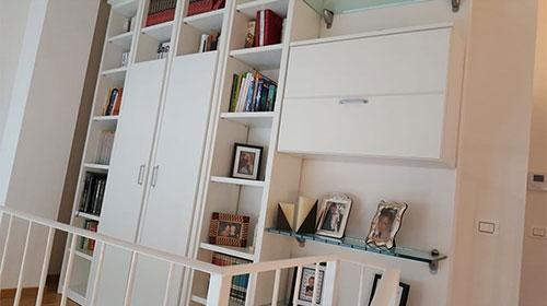 Libreria rilaccata da giallo avorio a bianco, tagliata modificata e aggiustata su muro stondato con cornici in massello a tamponamento
